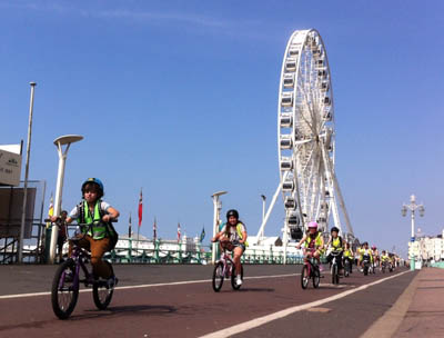 Children cycling past Brighton's big wheel